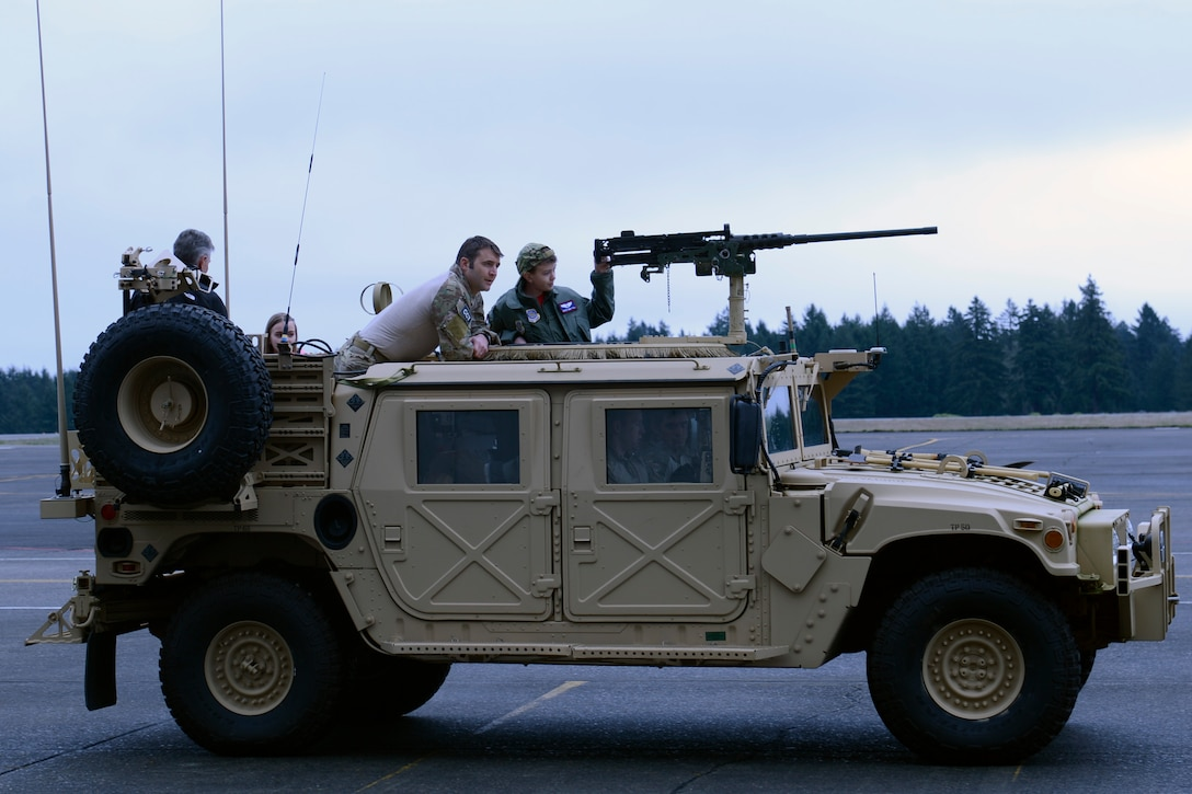 """Carver Faull, McChord Field's honorary Pilot for a Day, and his family take a ride on a Humvee, courtesy of the Airmen of the 22nd Special Tactics Squadron, Feb. 20, 2015, at Joint Base Lewis-McChord, Wash. """"This event has been so important to us,"""" said Chief Master Sgt. Jeff Guilmain, 22nd STS superintendent. """"We're happy to be a part of it."""" (U.S. Air Force photo/Senior Airman Rebecca Blossom)"""