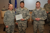 """PETERSON AIR FORCE BASE, Colo. – Master Sgt. Brian Beaty (left) 52nd Airlift Squadron acting first sergeant, and Capt. Aaron Bowens (right), 52nd AS maintenance officer, present the Diamond Sharp award to Senior Airman Isitolo Lautoa, 52nd AS aircraft hydrualics systems specialist, Feb. 11. Lautoa led a """"Redball"""" response team, identifying and replacing a steering control valve ahead of a two-hour standard, which enabled a presidential support mission. Additionally, he rebuilt and replaced a worn hydraulic test stand hose, saving the Air Force $300,000 for a new aircraft support equipment. (U.S. Air Force photo by Robb Lingley)"""