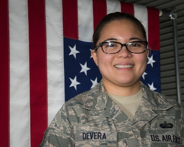 Tech. Sgt. Christine Devara poses in front of an American Flag in the departures section of the Charles C. Carson Center for Mortuary Affairs, Dover Air Force Base, Del., Feb. 23, 2015. Devara, currently serving on her seventh deployment to the mortuary, became a funeral director as a result of her experience here. She is a reservist with the 512th Memorial Affairs Squadron. (U.S. Air Force photo by Capt. Raymond Geoffroy)