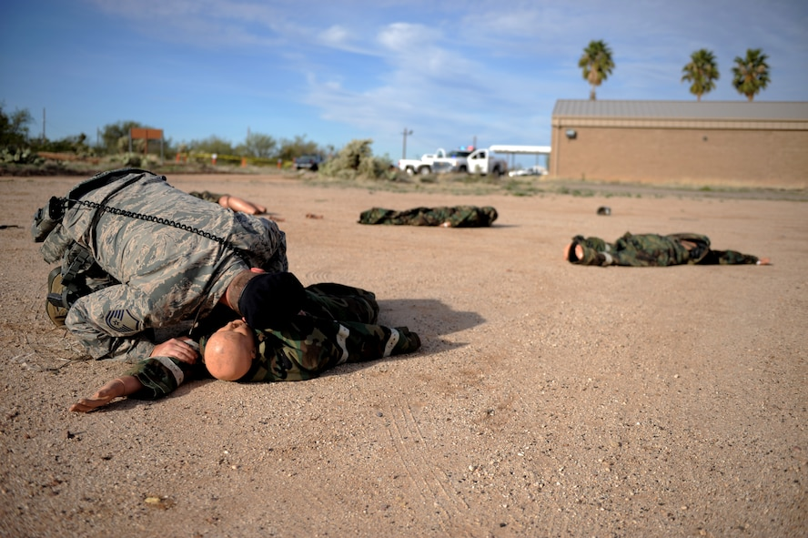 A U.S. Air Force Airman from the 355th Security Forces Squadron checks a simulated casualty's breathing during an aircraft crash exercise at Davis-Monthan Air Force Base, Ariz., Feb. 19, 2015. The exercise was held to test D-M's capabilities to respond to an aircraft crash incident with mass-casualties. (U.S. Air Force photo by Airman 1st Class Chris Drzazgowski/Released)