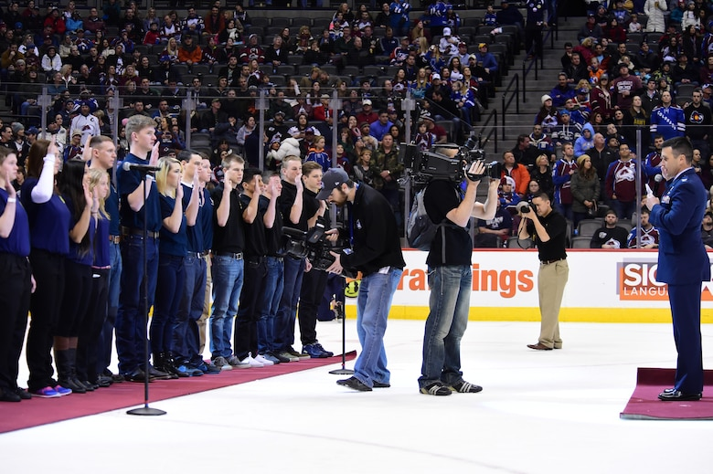 Col. John Wagner, 460th Space Wing commander, administers the Oath of Enlistment to military recruits Feb. 22, 2015, at the Pepsi Center in Denver.  Eighteen military recruits took the Oath of Enlistment during the second intermission of the game. (U.S. Air Force photo by Airman 1st Class Luke W. Nowakowski/Released)