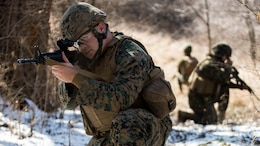 Cpl. Joseph Howell, a tactical switching operator with Combat Logistics Regiment 4, 4th Marine Logistics Group, kneels down and takes account of his surroundings on a patrol during the Marine Expeditionary Force Exercise in Kansas City, Mo., Feb. 22, 2015. Howell was part of the acting guard force during the exercise with I MEF. The exercise enabled Marines to improve interoperability between the active and Reserve component, while preparing them with a realistic training environment at the force level.