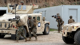 """The QRF security element posts up four-corner security around an objective site during a Quick Reaction Force drill, as part of Marine Expeditionary Force Exercise 2015 aboard Camp Pendleton, Calif., Feb. 22, 2015. Marines with 1st Law Enforcement Battalion employed a QRF to combat imminent """"enemy threats"""" during MEFEX-15."""