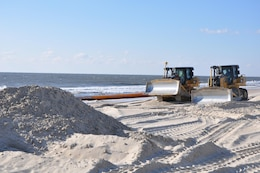 Bulldozers distribute newly-placed sand at Westhampton Beach, New York, November 21, 2014. The sand, pumped onto the beach from an approved offshore borrow site, repaired severe erosion caused by Hurricane Sandy in 2012. The Army Corps of Engineers, New York District, placed nearly 1 million cubic yards of sand for the Westhampton Beach Interim Project providing coastal storm risk reduction for nearly 4 miles of shoreline from Westhampton Beach to Cupsogue Beach County Park on Long Island's south shore. Work included berm and dune restoration, tapering an existing groin, and constructing a new groin. The project was completed in late 2014.