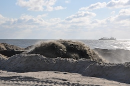 A mixture of sand and water pumping onshore at Westhampton Beach, New York, November 21, 2014. A dredge (background) collects sand from an approved offshore borrow site and  transports it to land via large underwater pipes. The Army Corps of Engineers, New York District, placed nearly 1 million cubic yards of sand for the Westhampton Beach Interim Project providing coastal storm risk reduction for nearly 4 miles of shoreline from Westhampton Beach to Cupsogue Beach County Park on Long Island's south shore. Work included berm and dune restoration, tapering an existing groin, and constructing a new groin. The project was completed late 2014.