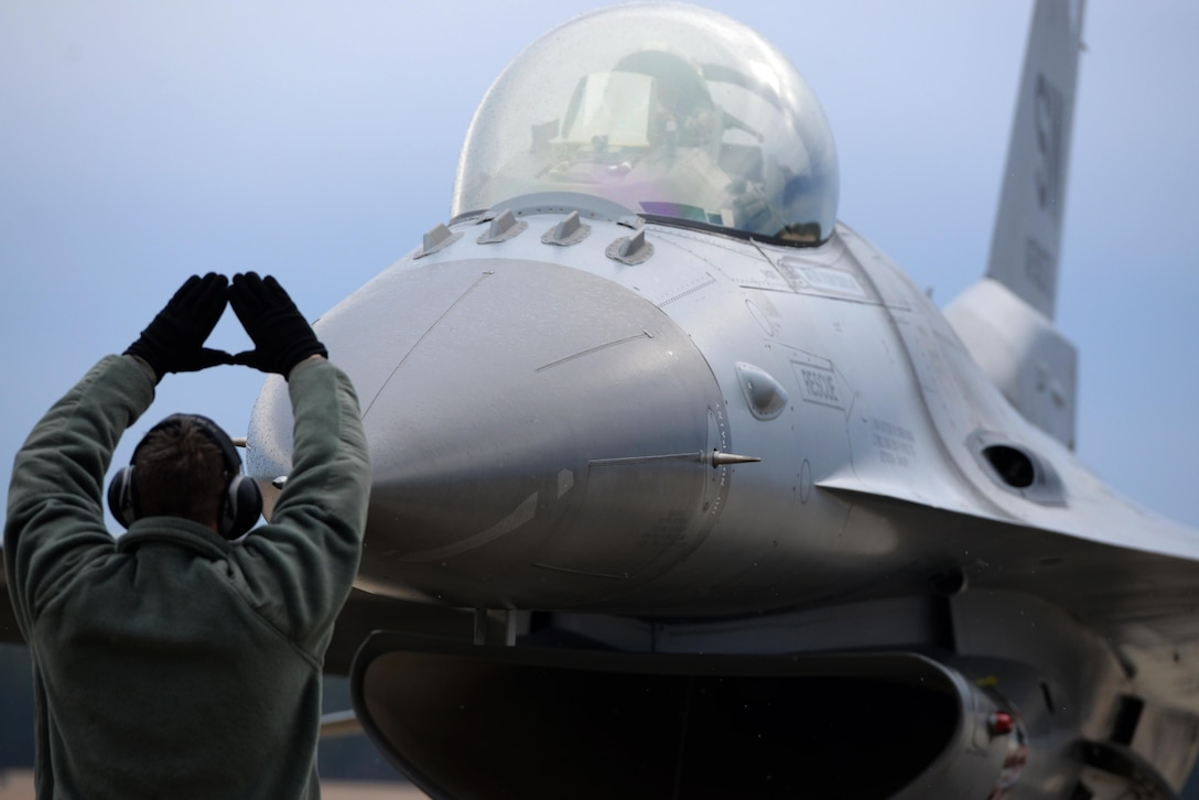 An Airman marshals an F-16 Fighting Falcon to a stop Feb. 5, 2015, at Shaw Air Force Base, S.C. The mission of the 20th Fighter Wing is to provide combat ready airpower and Airmen, to meet any challenge, anytime, anywhere. The Airman is assigned to the 20th Aircraft Maintenance Squadron. (U.S. Air Force photo/Airman 1st Class Jonathan Bass)