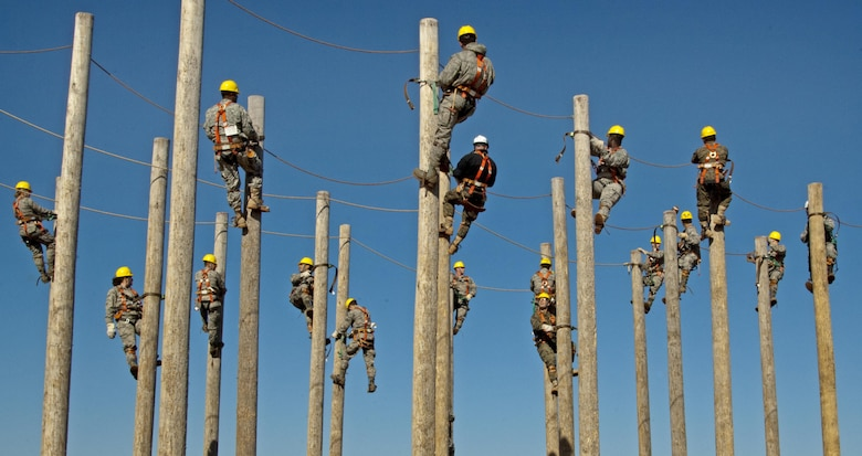 Students of the 364th Training Squadron's electrical systems course practice climbing power poles as part of a familiarization and trust exercise with the safety equipment Feb. 3, 2015, at Sheppard Air Force Base, Texas. They spent an extended period suspended to simulate a lengthy installation or repair as part of the training. (U.S. Air Force photo/Danny Webb)