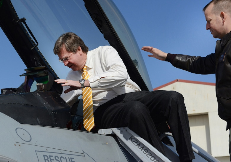 Maj. Chris Wells explains proper and safe entry into an F-16 Fighting Falcon cockpit to Tulsa Mayor Dewey F. Bartlett, Jr. during a visit February 25, 2015 at the Tulsa Air National Guard base, Tulsa, Okla. The mayor was hosted by 138th leadership as a community outreach event aimed at fostering good relations and educating local leaders on the mission of the wing.