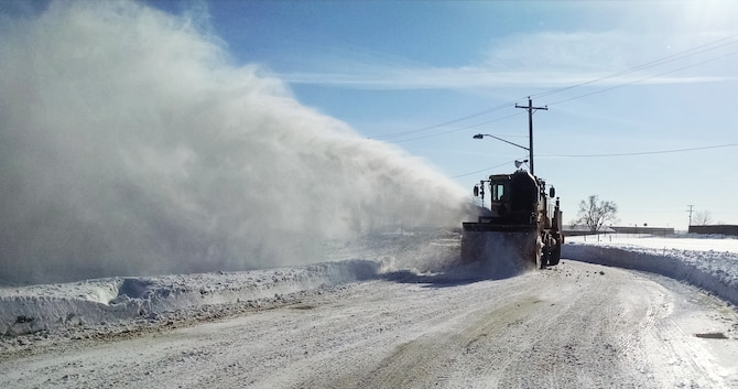 Pegasus Support Services, the snow removal team for Niagara Falls Air Reserve Station, blows snow into a vacant field off of an access road on base, February 25, 2015. Snow accumulation for the Western New York region has been so extreme that plows have run out of places on base to dump the snow. (Courtesy Photo)