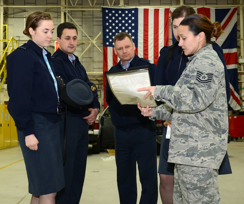 U.S. Air Force Tech. Sgt. Amy Chandler, right, 100th Logistics Readiness Squadron Vehicle Maintenance NCO in charge of general purpose vehicles from New Orleans, La., briefs Royal Air Force members on a vehicle and equipment work order, during a tour of the 100th LRS  Feb. 24, 2015, on RAF Mildenhall, England. RAF Logistics officers visited with members of the 100th LRS during a site tour to further improve relations between the two nations. (U.S. Air Force photo by Gina Randall/Released)