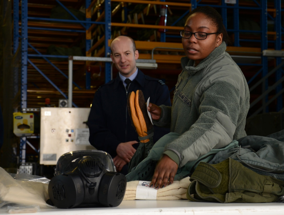 U.S. Air Force Airman 1st Class Andrea Blackmon, right, 100th Logistics Readiness Squadron Individual Protective Equipment mobility apprentice from Miami, Fla., shows equipment and clothing to Royal Air Force Logistics officers during a tour of the LRS squadron Feb. 24, 2015, on RAF Mildenhall, England. Members of the RAF visited with members of the 100th LRS during a site tour to further improve relations between the two nations. (U.S. Air Force photo by Gina Randall/Released)