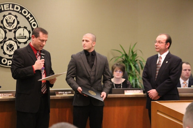 """Billy Smith (left), Principal of Fairfield High School, speaks to Fairfield city council during a city council meeting, Jan 9, about the courageous acts John Jones (center), an 18-year-old Fairfield High School senior, performed when a substitute teacher collapsed in class. Fairfield Mayor Steve Miller (right) proclaimed January 9, 2015 """"John Jones Day."""" After the proclamation, Jones participated in a ceremonial oath of enlistment to join the United States Marine Corps. (Marine Corps photo by Sgt. Jennifer Pirante/Released)"""