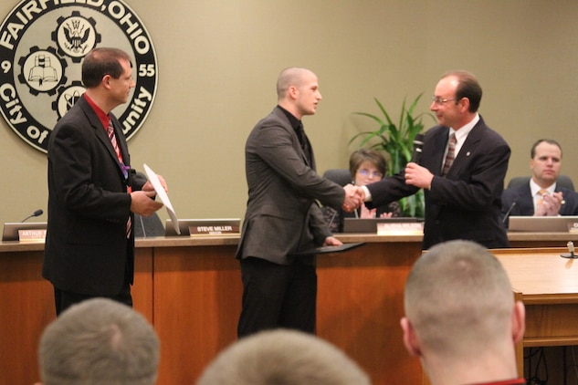 """Fairfield City Council and Mayor Steve Miller (right) thanks John Jones (center), an 18-year-old Fairfield High School senior, during a Fairfield city council meeting, Jan 9, for saving the life of a substitute teacher who had collapsed in class.  After the council proclaimed the day as """"John Jones Day,"""" Jones participated in a ceremonial oath of enlistment to join the United States Marine Corps. (Marine Corps photo by Sgt. Jennifer Pirante/Released)"""