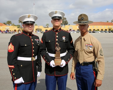 U.S. Marine Corps Pfc. Mason V. Meyer (center), of Platoon 2106, Company E, 2nd Recruit Training Battalion, poses for a photograph with, his recruiter Sgt. Benjamin R. Saraceno (left), Recruiting Sub Station Reno, Recruiting Station Sacramento, 12th Marine Corps District, and his Senior Drill Instructor SSgt. Vicenti R. Ervin (right), of Platoon 2106, Company E, 2nd Recruit Training Battalion after a graduation ceremony at Marine Corps Recruit Depot San Diego, Calif., Feb. 27. Meyer, of Reno, Calif., received the Chesty Puller award and was named Company Honor Graduate from Company E, 2nd Recruit Training Battalion. (U.S. Marine Corps photo by Pfc. Kent Springfield/Released)