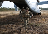 U.S. Marines with the 22nd Marine Expeditionary Unit exit an MV-22 Osprey aircraft at Marine Corps Base Camp Lejeune, N.C., Feb. 27, 2015. The unit conducted a seven-mile hike to maintain unit readiness and build morale. (U.S. Marine Corps photo by Cpl. Caleb McDonald/Released)
