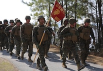 U.S. Marine Corps Sgt. Samuel Mosley, 22nd Marine Expeditionary Unit (MEU) fiscal chief and native of Devers, Texas, carries the unit guideon during a seven-mile hike at Marine Corps Base Camp Lejeune, N.C., Feb. 27, 2015. The unit conducted the hike to maintain unit readiness and build morale. (U.S. Marine Corps photo by Cpl. Caleb McDonald/Released)