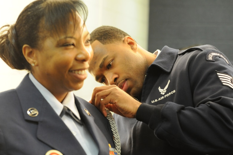 Tech. Sgt. Marcus Boykin helps Tech. Sgt. Jaqueline Constance with her Honor Guard uniform prior to presenting the colors during the Washington Wizards home game against the Golden State Warriors, Feb. 24. Both Boykin and Constance are D.C. Air National Guard participating in a community appreciation night honoring the DCANG.  (Air National Guard photo by Master Sgt. Craig Clapper)