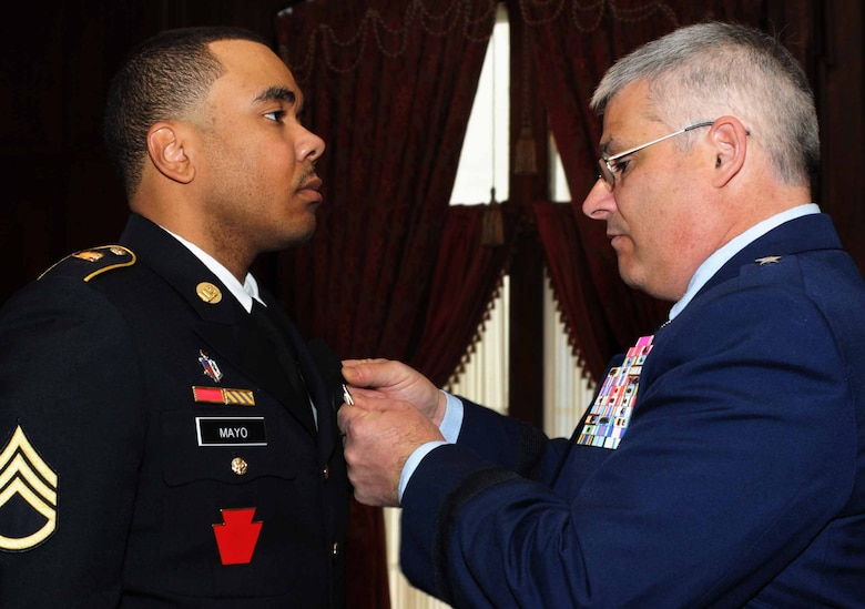 Brig. Gen. Tony Carrelli, Deputy Adjutant General-Air, Pennsylvania National Guard, Joint Force Headquarters at Fort Indiantown Gap, Pennsylvania, bestows the Major Octavius V. Catto Medal upon Staff Sgt. Melvyn L. Mayo Jr., Medical Battalion Training Site instructor, Fort Indiantown Gap, Feb. 21, 2015, at The Union League of Philadelphia, Philadelphia, Pennsylvania. The award bears the name of the Civil War-era African American leader and civil rights martyr from Philadelphia and is awarded to Guardsmen who display exemplary service and community support. (U.S. Air National Guard photo by Tech. Sgt. Andria J. Allmond/Released)