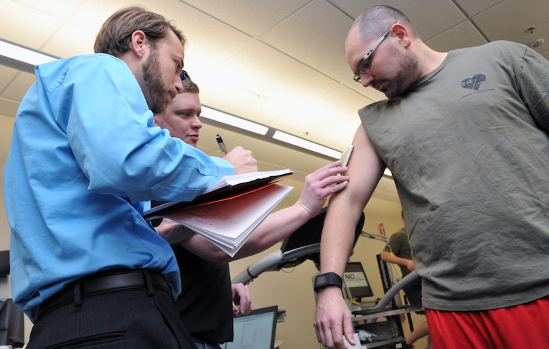 Researcher, Dr. Gavi Begtrup, and University of Cincinnati doctoral student, Daniel Rose, read Air Force Research Laboratory researcher, Dr. Joshua Hagen's, sweat sensor using a smartphone app. The sensor, which is worn like a Band-Aid, tracks the user's level of hydration, among other crucial markers of the body's state after exercise. The research team, including the Air Force Research Laboratory's 711th Human Performance Wing and the University of Cincinnati's Novel Devices lab, conducted the first successful human trials of a usable sweat sensor prototype at Wright-Patterson Air Force Base, Ohio, Feb. 11. (U.S. Air Force photo by Michele Eaton/88 ABW Public Affairs/Released)