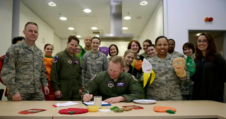 U.S. Air Force Col. Joe McFall, 52nd Fighter Wing commander, seated center, signs a proclamation alongside base community members during a National Nutrition Month kickoff event in the Spangdahlem Health Promotion's kitchen at Spangdahlem Air Base, Germany, Feb. 26, 2015. The proclamation designated the month of March as National Nutrition Month and encouraged Spangdahlem community members to make informed food choices and develop sound eating and physical activity habits. (U.S. Air Force photo by Airman 1st Class Timothy Kim/Released)