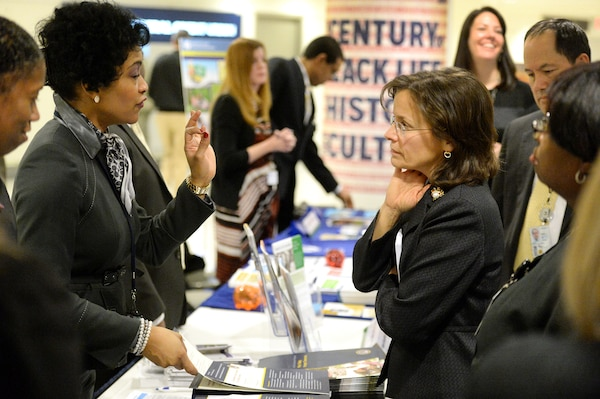 "Rosemary Freitas Williams, deputy assistant secretary of defense for military community and family policy, right, converses with Monica Keitt of the Veterans Administration Insurance Service at the Military Saves Week Financial Fair at the Pentagon, Feb. 23, 2015. ""The Department of Defense is happy to have had an active role in Military Saves Week since 2007. This campaign is an important opportunity to focus on healthy financial practices that we know are important to all of our service members and their families every day of the year,"" Williams said. DoD photo by EJ Hersom"