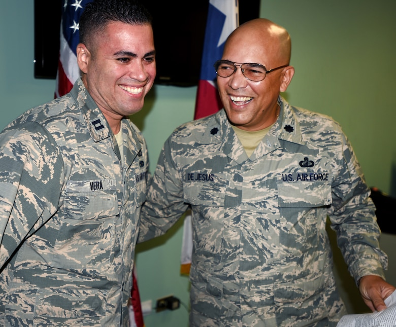 Capt. Carlos Vera, former Budget Officer (Left) for the 156th Airlift Wing happily takes over the 156th Comptroller Flight Command from Lt. Col. Victor Dejesus who will be assigned to the Puerto Rico National Guard Joint Forces Headquarters in San Juan. In the brief change of command ceremony, Vera accepts his position during the Unit Training Assembly at Air National Guard Base Muñiz on Jan. 24, 2014 . (U.S. Air National Guard photo by Tech. Sgt. Marizol Ruiz/Released)