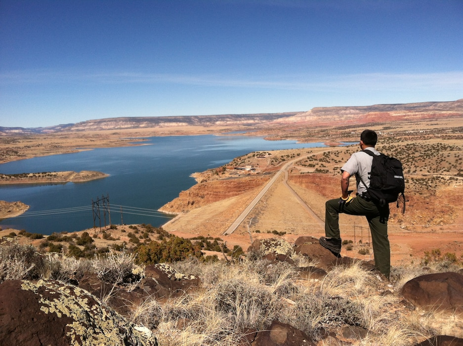 """Abiquiu Park Ranger Nathaniel Naranjo inspects fence line above Abiquiu Dam."" Photo by Austin Kuhlman, March 9, 2014."