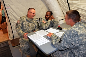 From left, Army Chaplain (Maj.) Alfred Grondski, who hails from Trenton, N.J., talks to Army Spc. Tamisha Cook, a Oviedo, Fla., native, both of Headquarters and Headquarters Company, 36th Engineer Brigade, and Army Pfc. Addison Cook, a Berryville, Ark., native with the 50th Signal Battalion, 35th Signal Brigade, Fort Bragg, N.C., about the upcoming New Year during a prayer breakfast at the National Police Training Academy in Paynesville, Liberia, Dec. 31, 2014. Operation United Assistance provides logistics, training and engineering support to U.S. Agency for International Development-led efforts to contain the Ebola virus outbreak in western Africa. U.S. Army photo by Sgt. Ange Desinor