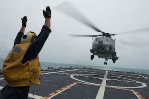 U.S. Navy Petty Officer 2nd Class Adam Garnett signals an MH-60R Sea Hawk helicopter from Helicopter Maritime Strike Squadron 35 on the flight deck of the littoral combat ship USS Fort Worth, Jan. 3, 2015. Fort Worth is currently in the Java Sea conducting helicopter search operations with the USS Sampson as part of Indonesian-led efforts to locate downed AirAsia Flight 8501. U.S. Navy photo by Petty Officer 2nd Class Antonio P. Turretto Ramos