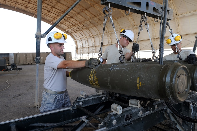 From left, Tech. Sgt. Stephen, shift lead, Senior Airman Adam and Airman 1st Class Luis, both munitions crew chief, load MK-82s onto a rail assembly Dec. 21, 2014, in Southwest Asia.  The Airmen are preparing to assemble 24 GBU-38s in preparation for real-world combat sorties.  Stephen is deployed from Joint Base Elmendorf-Richardson, Alaska, and Adam and Luis are deployed from Seymour Johnson Air Force Base, N.C.  (U.S. Air Force photo/Senior Master Sgt. Carrie Hinson)