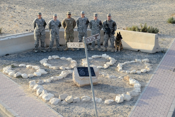 SOUTHWEST ASIA - Airmen from the 386th Expeditionary Security Forces Squadron stand behind the rebuilt Security Forces K9 memorial here Dec. 28, 2014. The original memorial, dedicated to Tech. Sgt. Jason L. Norton and Staff Sgt. Brian McElroy, was damaged in a vehicle accident in September. (U.S. Air Force photo by Tech. Sgt. Jared Marquis/released)