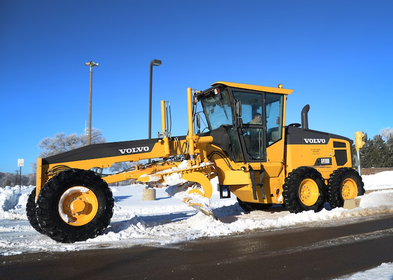 U.S. Air Force Senior Airman Corey Masquef, 27th Special Operations Civil Engineer Squadron pavement and construction equipment apprentice, operates a motor grader to clear snow near the main gate Jan. 5, 2015 at Cannon Air Force Base, N.M. Members of the 27th Special Operations Wing should remain patient while this on-going effort continues by the 27 SOCES team, and maintain vigilance while exercising caution during commutes. (U.S. Air Force photo/Staff Sgt. Alexxis Mercer)