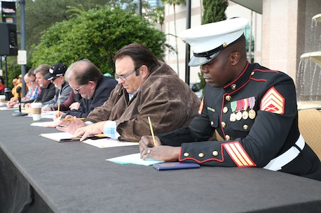 Staff Sgt. Santwan Odom, Musical Technical Assistant for the 6th Marine Corps District, critiques bands along with the rest of the judging panel January 1, 2015 at the Jacksonville Landing in Jacksonville, Fla., for the 2015 TaxSlayer Bowl game. The Bands on Parade event included the Parris Island Marine Band, marching bands from the Universities of Tennessee and Iowa and high school bands from around the country. The Marine Corps has partnered with the bowl for nine consecutive years. (Official Marine Corps photo by Cpl. John-Paul Imbody)
