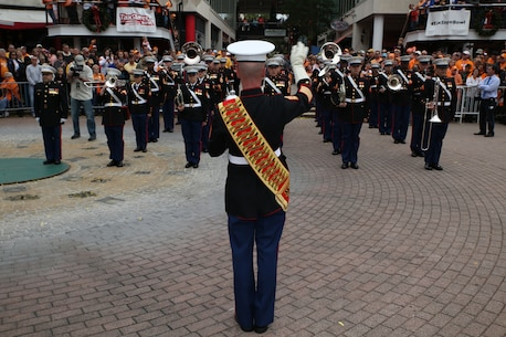 Gunnery Sgt. David Wilson, the Parris Island Marine Band Drum Major, leads the Marine band during a pep rally January 1, 2015 at the Jacksonville Landing in Jacksonville, Fla., for the 2015 TaxSlayer Bowl game. The Bands on Parade event included the Parris Island Marine Band, marching bands from the Universities of Tennessee and Iowa and high school bands from around the country. The Marine Corps has partnered with the bowl for nine consecutive years. (Official Marine Corps photo by Cpl. John-Paul Imbody)