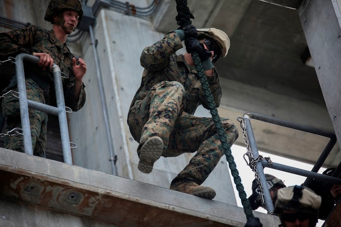 Marines hone their fast-roping skills Dec. 3 at the Camp Hansen rappel tower. The Marines gradually increased the difficulty, first rappelling without gear, then with their flak vests, and finally with their weapons. The Marines are with Company F, Battalion Landing Team 2nd Battalion, 4th Marines, 31st Marine Expeditionary Unit. (U.S. Marine Corps photo by Lance Cpl. Ryan C. Mains/Released)