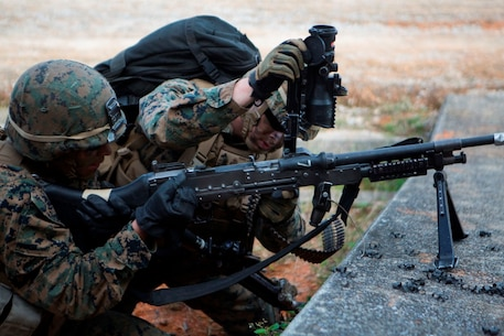 U.S. Marines with Company E, Battalion Landing Team 2nd Battalion, 4th Marines, (BLT) 31st Marine Expeditionary Unit, reload an M240 Machine Gun while conducting a vertical assault at Combat Town, Okinawa, Japan, Dec. 8, 2014. Company E is conducting training as part of the MEU Exercise and pre-deployment training. (U.S. Marine Corps Photo by Lance Cpl. Richard Currier/ Released)