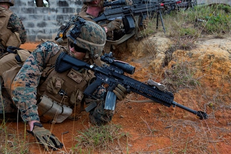 U.S. Marine Corps Lance Cpl. Thomas Hardy, rifleman, Company E, Battalion Landing Team 2nd Battalion, 4th Marines, (BLT) 31st Marine Expeditionary Unit, yells orders to other Marines while conducting a vertical assault at Combat Town, Okinawa, Japan, Dec. 8, 2014. Company E is conducting training as part of the MEU Exercise and pre-deployment training. (U.S. Marine Corps Photo by Lance Cpl. Richard Currier/ Released)
