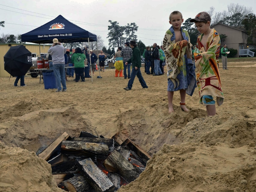 Participants warm up next to a fire pit on the beach after their plunge into Lake Moultrie as part of the inaugural Polar Plunge at the Joint Base Charleston Short Stay Recreation Area, Jan. 3, 2014. (U.S. Air Force photo/Jessica Donnelly)