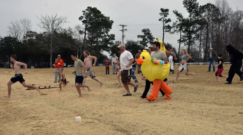 Polar Plunge participants race toward the chilly waters of Lake Moultrie as part of the inaugural Polar Plunge at the Joint Base Charleston Short Stay Recreation Area, Jan. 3, 2014. Nearly 20 people took the plunge while others watched on as they enjoyed hot chocolate and hot dogs. (U.S. Air Force photo/Jessica Donnelly)