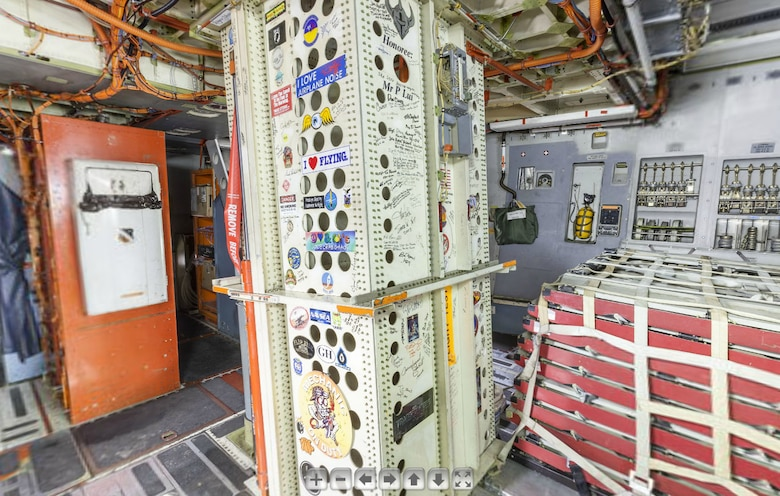 """This screenshot shows the forward cargo area inside the Boeing C-17 Globemaster III on the National Museum of the U.S. Air Force's Virtual Tour website. In the bottom center of the photo, you can see stickers from the """"Transformers"""" and """"Iron Man"""" movies, along with autographs from """"Iron Man"""" stars Robert Downey Jr. and Gwyneth Paltrow and director Jon Favreau. (U.S. Air Force image)"""