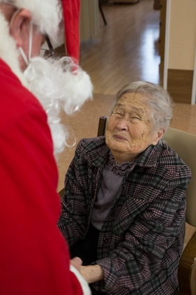 Retired Coast Guard Petty Officer 1st Class Elder Hal Pierce, a service missionary with the Church of Jesus Christ of Latter-day Saints, dressed as Santa, greets a resident of Nadamien Nursing Home in Iwakuni City, Japan, during a community relations event, Dec. 19, 2014. Volunteers from Marine Corps Air Station Iwakuni sang for and interacted with the residents. This event was made to build a stronger bond between the U.S. and Japan.