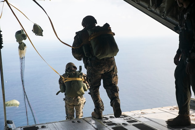 IE SHIMA, OKINAWA, Japan — Marines static line jump out of a KC-130J Super Hercules aircraft Nov. 20, 2014 over Ie Shima Training Facility, off the northwest coast of Okinawa, Japan. While performing a low level static line jump, the jumper is released from the aircraft at a low altitude and their chute is pulled open by the aircraft as they exit. The Marines did their static line jumps from an altitude of 1,500 feet for this training. The Marines are with 3rd Reconnaissance Battalion, 3rd Marine Division, III Marine Expeditionary Force.