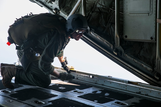 Gunnery Sgt. Matthew Bateman peers out the rear of a KC-130J Super Hercules aircraft Nov. 20, 2014 over Ie Shima Training Facility, off the northwest coast of Okinawa, Japan. Marines with 3rd Reconnaissance Battalion were conducting parachute training, keeping them proficient and current with their jump qualifications. Bateman, from Gaithersburg, Maryland, is a reconnaissance man and jumpmaster with 3rd Recon Bn., 3rd Marine Division, III Marine Expeditionary Force.