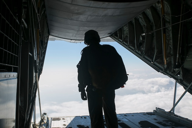 Gunnery Sgt. Matthew Bateman peers out the rear of a KC-130J Super Hercules aircraft Nov. 20, 2014 over Ie Shima Training Facility, off the northwest coast of Okinawa, Japan. Marines with 3rd Reconnaissance Battalion took part in parachute training, keeping them proficient and current with their jump qualifications. Bateman, from Gaithersburg, Maryland, is a reconnaissance man and jumpmaster with 3rd Recon Bn., 3rd Marine Division, III Marine Expeditionary Force.