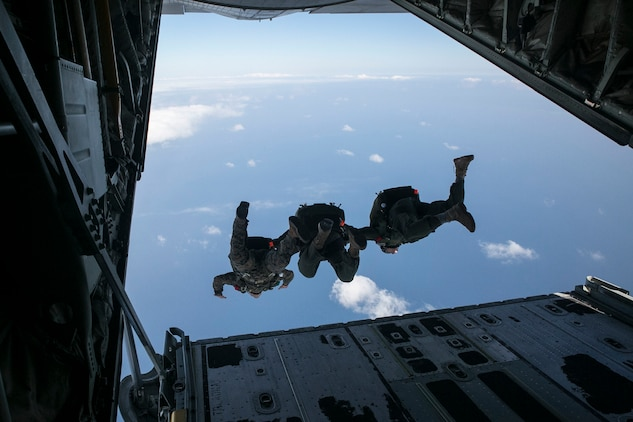 Gunnery Sgt. Gabriel Machado, left, Master Sgt. Raul Argumedo, center, and Gunnery Sgt. Matthew Bateman jump in tandem from a KC-130J Super Hercules aircraft Nov. 20, 2014 over Ie Shima Training Facility, off the northwest coast of Okinawa, Japan. The Marines jumped from an altitude of 10,000 feet during the high speed training. Machado, from New York, New York, is an air delivery specialist with 3rd Reconnaissance Battalion, 3rd Marine Division, III Marine Expeditionary Force. Argumedo, from Los Angeles, California, is an air delivery specialist with the battalion. Bateman, from Gaithersburg, Maryland, is a reconnaissance man with the battalion.