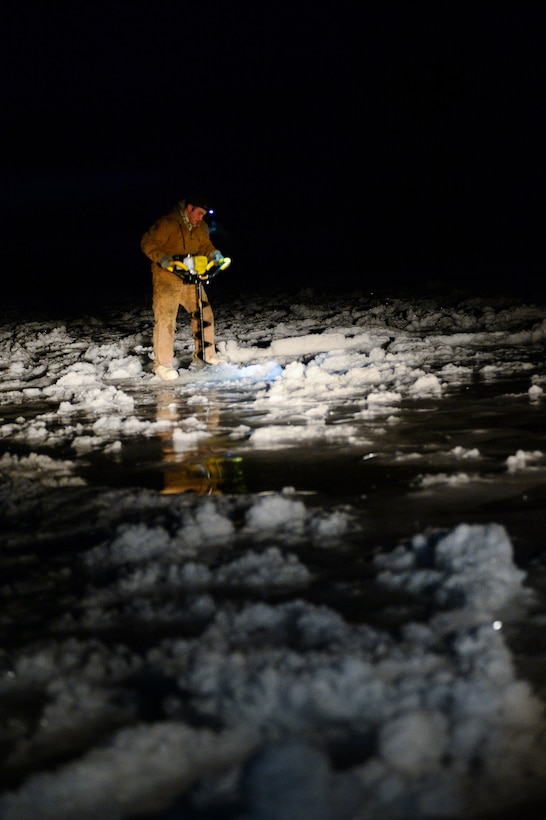 Senior Airman Tyler Dray uses an ice auger while constructing an ice bridge in Fairbanks, Alaska, Nov. 20, 2014. The bridge must be constructed every other year to provide access to the $20 million range complex used to train pilots from around the world during Red Flag-Alaska exercises. Dray is a range maintenance structures journeyman assigned to the 354th Civil Engineer Squadron. (U.S. Air Force photo/Staff Sgt. Shawn Nickel)