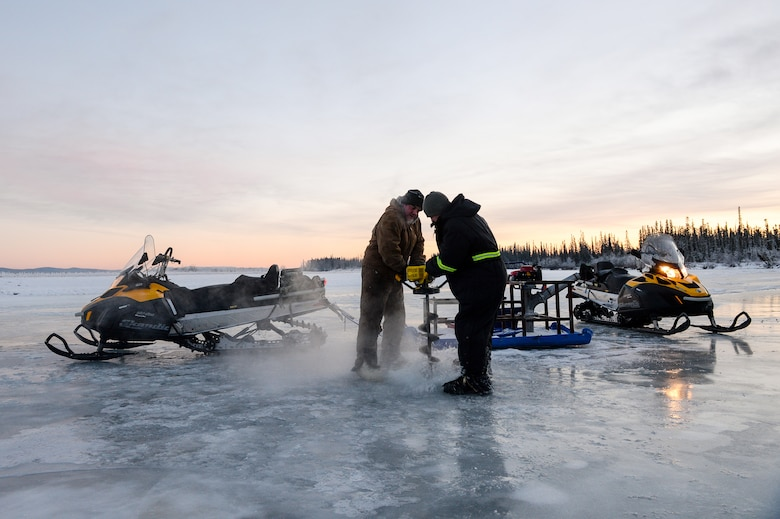 Senior Airmen Tyler Dray and Jerry Mitchell use an ice auger Nov. 20, 2014, while constructing an ice bridge in Fairbanks, Alaska. The bridge must be constructed every other year to provide access to the $20 million range complex used to train pilots from around the world during Red Flag-Alaska exercises. Dray is a range maintenance structures journeyman and Mitchell is a heavy equipment operator with the 354th Civil Engineer Squadron on Eielson Air Force Base, Alaska. (U.S. Air Force photo/Staff Sgt. Shawn Nickel)