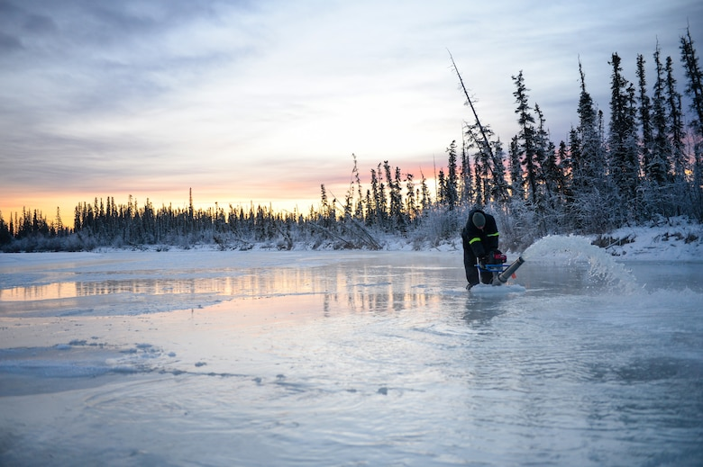 Senior Airman Jerry Mitchell uses a water pump Nov. 20, 2014, while constructing an ice bridge in Fairbanks, Alaska. The bridge must be constructed every other year to provide access to the $20 million range complex used to train pilots from around the world during Red Flag-Alaska exercises. Mitchell is a heavy equipment operator with the 354th Civil Engineer Squadron on Eielson Air Force Base, Alaska.  (U.S. Air Force photo/Staff Sgt. Shawn Nickel)