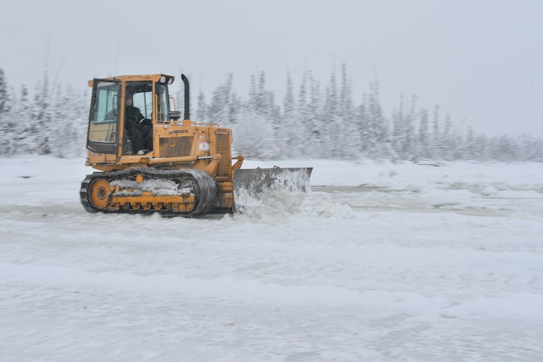 Senior Airman Zach Harter uses a bulldozer to build an ice bridge Dec. 2, 2014, in Fairbanks, Alaska. The bridge must be constructed every other year to provide access to the $20 million range complex used to train pilots from around the world during Red Flag-Alaska exercises. Harter is a heavy equipment operator assigned to the 354th Civil Engineer Squadron on Eielson Air Force Base, Alaska. (U.S. Air Force photo/Tech. Sgt. Joseph Swafford)