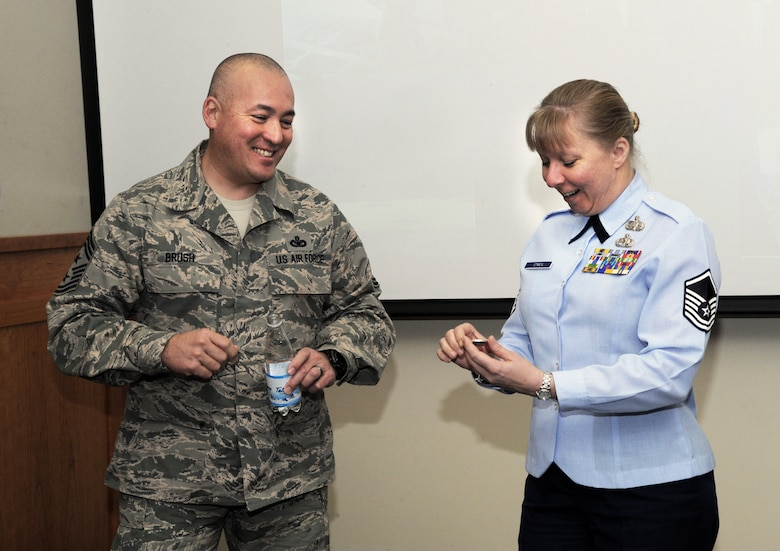 Chief Master Sgt. Mitchell O. Brush, Senior Enlisted Advisor for the National Guard Bureau, left, gives one of his coins to Master Sgt.  Anja O'Neil, assigned to the 123rd Fighter Squadron, right, during his visit to the Portland Air National Guard Base, Ore., Jan. 5, 2015. Chief Brush toured the air base and led a town hall event to highlight the changes and challenges that Soldiers and Airmen of the National Guard face going into the New Year. (U.S. Air National Guard photo by Tech. Sgt. John Hughel, 142nd Fighter Wing Public Affairs/Released)